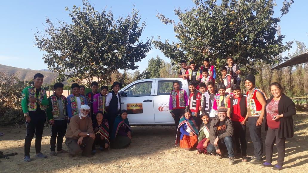 Multitud de personas, jóvenes, niños, trabajadores de K'anchay posando junto a Roberto bajo unos árboles