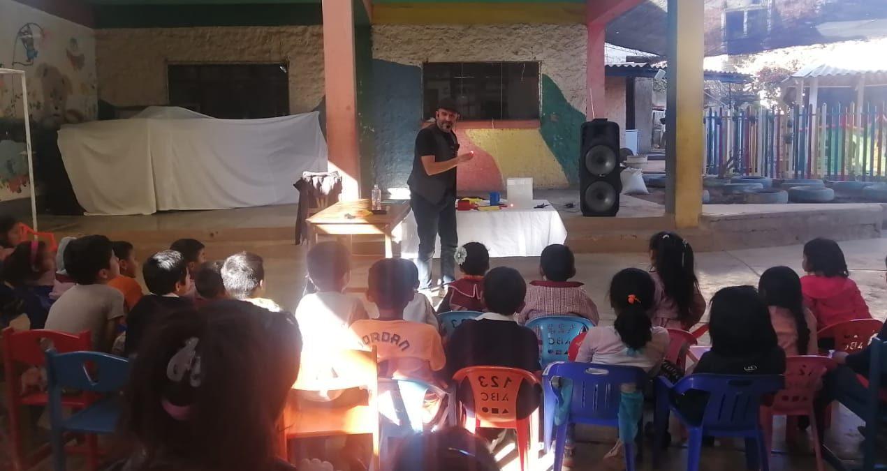 Roberto en un colegio haciendo un taller de magia con un grupo de niños y niñas