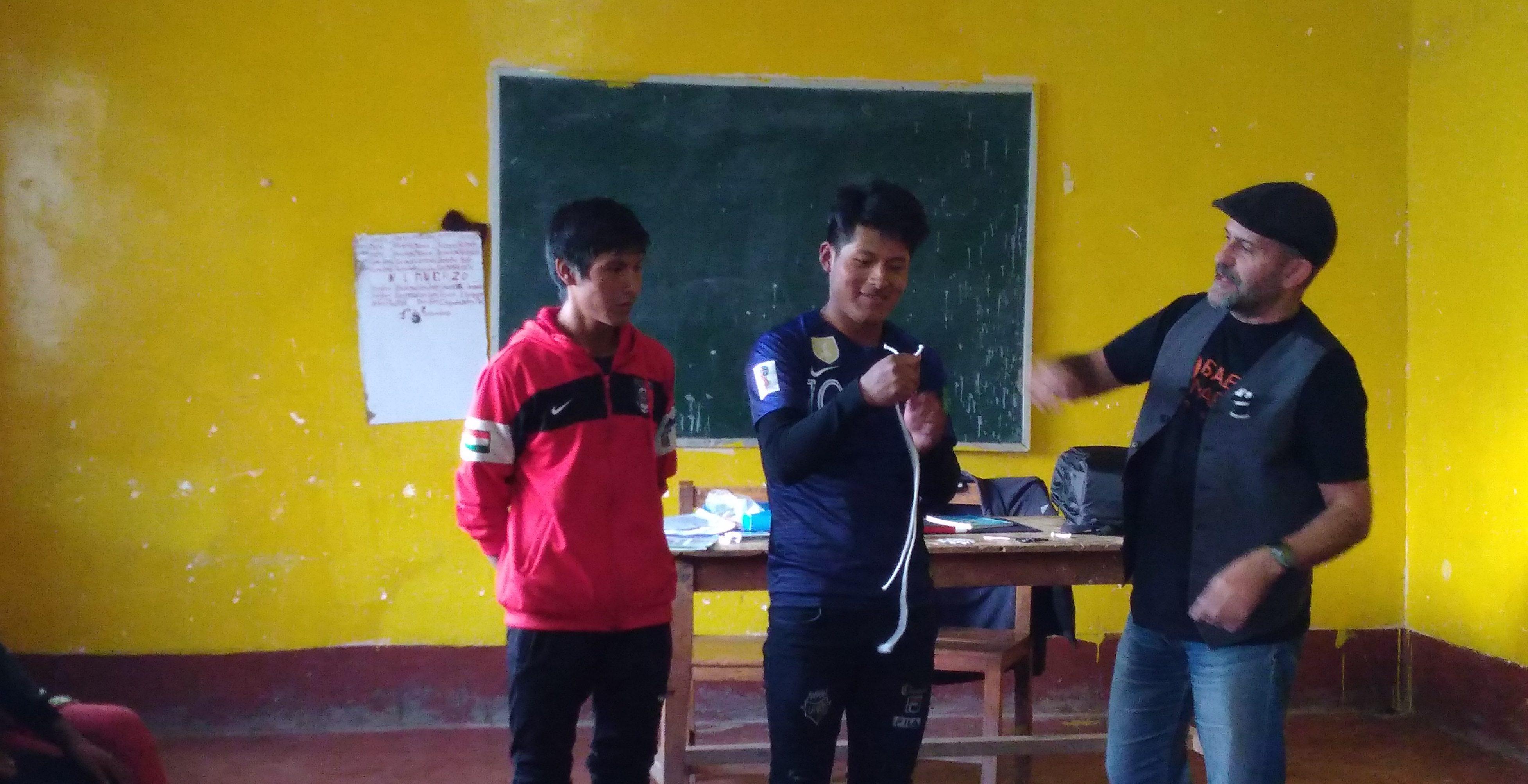Roberto con dos jóvenes realizando un taller de magia