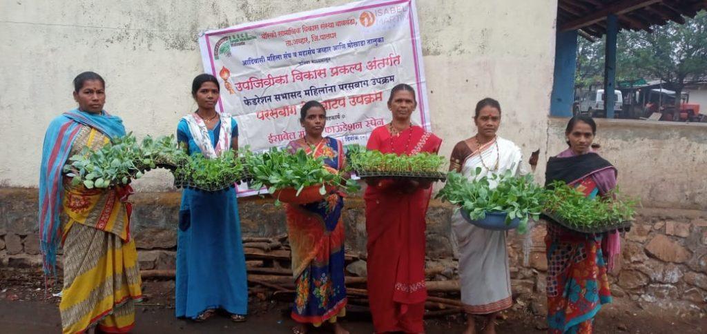 Varias mujeres beneficiarias muestran los plantones para sus huertosen el distrito de Palghar, en el estado de Maharashtra (India)
